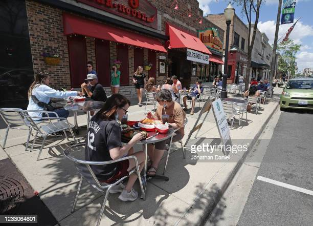 Diners eat lunch on the sidewalk in front of Casa Margarita restaurant on May 29, 2020 in LaGrange, Illinois. Phase 3 of Illinois governor J.B....