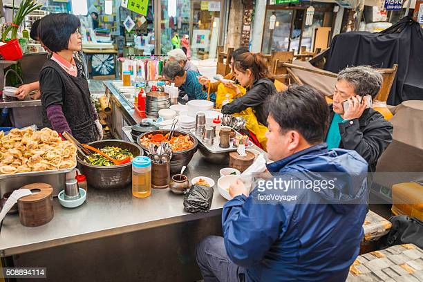 Diners eating traditional food at market stall Seoul South Korea
