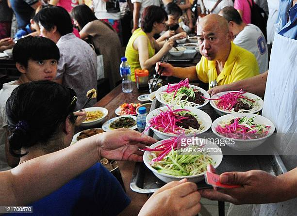 Diners enjoy bowls of 'Pork Noodles in Brown Bean Sauce' in the crowded the Yaoji Chaogan restaurant after the restaurant's popularity soared due to...