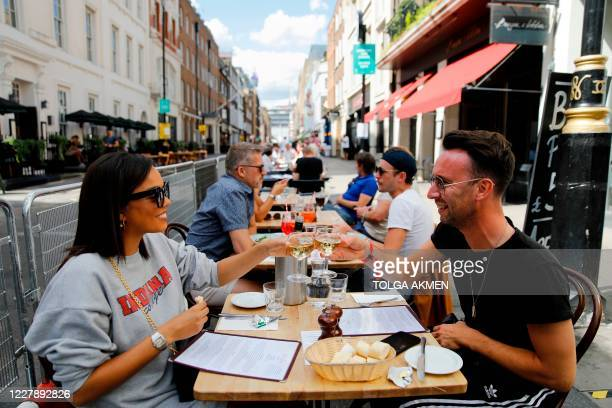 "Diners enjoy their drinks as they sit at tables outside a restaurant in London on August 3 as the Government's ""Eat out to Help out"" coronavirus..."