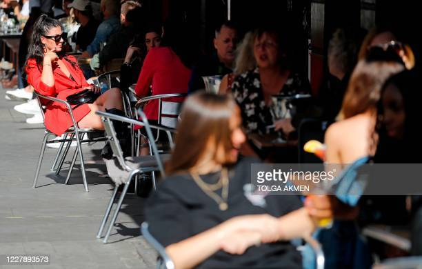 """Diners enjoy their drinks as they sit at tables outside a restaurant in London on August 3 as the Government's """"Eat out to Help out"""" coronavirus..."""