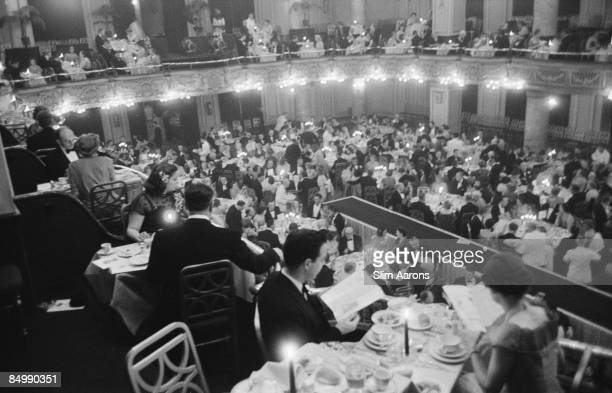 Diners in a grand ballroom during a fashion show circa 1955
