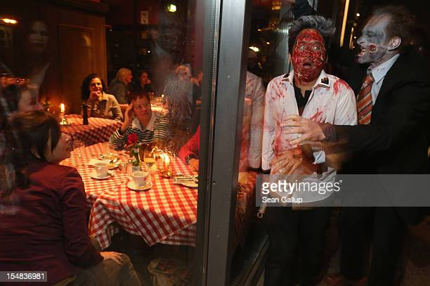 Diners in a restaurant look on as zombie enthusiasts walk by during a 'Zombie Walk' in the city center on October 27 2012 in Berlin Germany...