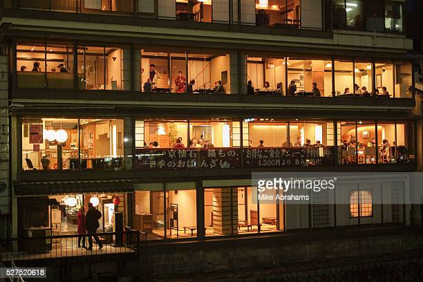 Diners seen through the windows of a riverside restauant on the banks of the Kamogawa River Kyoto Japan