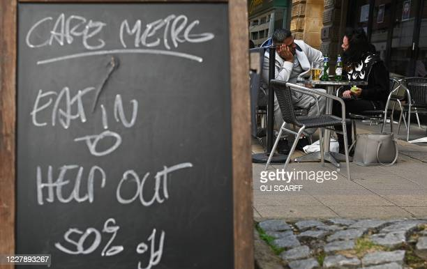 """Diners sit at table near a sign promoting the British Government's """"Eat out to Help out"""" COVID-19 scheme to get consumers spending again, outside a..."""