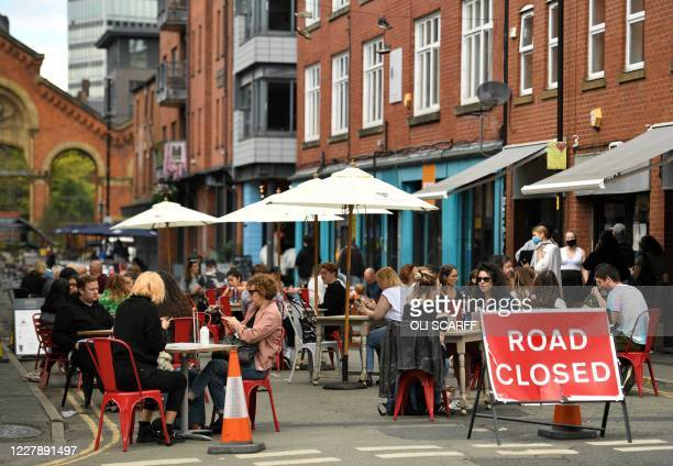 Diners sit at tables in a closed-off road, allowing restaurants to increase their outdoor seating to enable social distancing, in Manchester,...