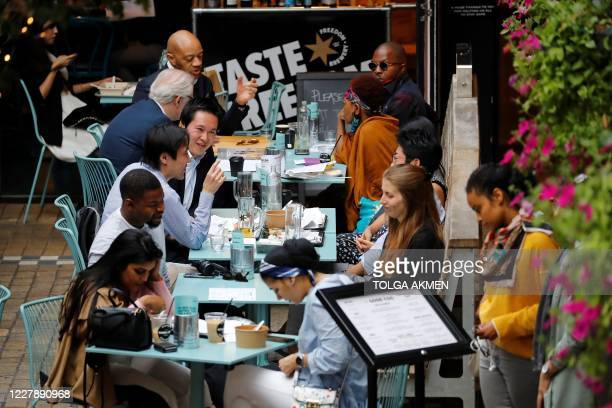 """Diners sit at tables outside a restaurant in London on August 3 as the Government's """"Eat out to Help out"""" coronavirus scheme to get consumers..."""
