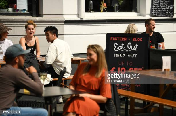 "Diners sit near a sign promoting the British Government's ""Eat out to Help out"" COVID-19 scheme to get consumers spending again, outside a restaurant..."