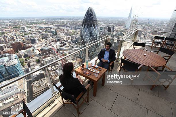 Diners sit on the roof terrace of the Sushisamba restaurant overlooking the Swiss Re tower also known as the 'Gherkin' center and the Shard...