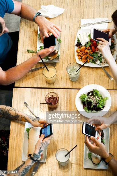 Diners using smartphones in restaurant, cropped overhead view