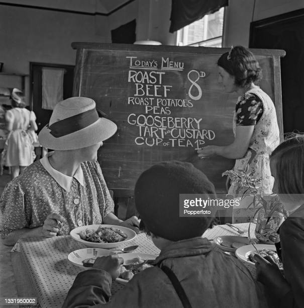 Diners watch a waitress chalk up a variety of dishes offered for today's menu on a blackboard at a recently opened British Restaurant in Gillingham,...