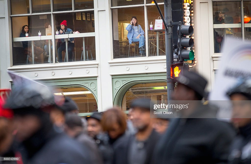 Diners watch from a restaurant window as demonstrators led by Rev. Jesse Jackson march through downtown to protest the death of Laquan McDonald and the alleged cover-up that followed on December 6, 2015 in Chicago, Illinois. Chicago Police officer Jason Van Dyke shot and killed 17-year-old McDonald on October 20, 2014, hitting him with 16 bullets. Van Dyke was charged with murder more than a year after the shooting after a judge ordered the release to the public of a video which showed McDonald backing away from Van Dyke while being shot.