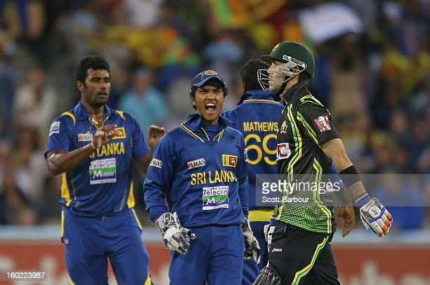 Dinesh Chandimal of Sri Lanka celebrates as Glenn Maxwell of Australia walks from the field after the final ball of the game during game two of the...