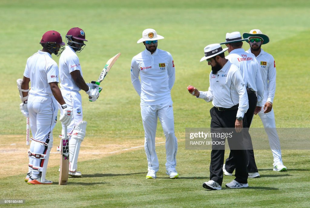 Dinesh Chandimal (C) of Sri Lanka look at the ball in umpire Aleem Dar's hand while Shai Hope (L) and Devon Smith (2L) of West Indies watch during day 3 of the 2nd Test between West Indies and Sri Lanka at Daren Sammy Cricket Ground, Gros Islet, St. Lucia, on June 16, 2018.