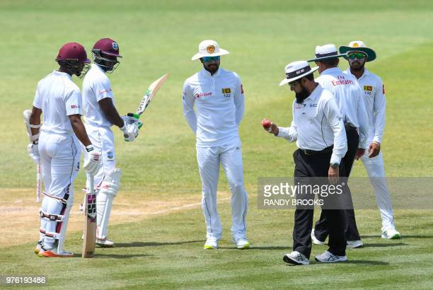 Dinesh Chandimal of Sri Lanka look at the ball in umpire Aleem Dar's hand while Shai Hope and Devon Smith of West Indies watch during day 3 of the...