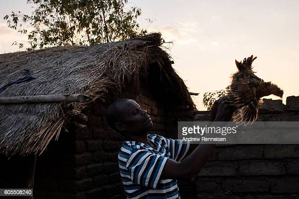 Dinesi Majawa holds a chicken at his family home in the village of Masale which lies in one of the areas most affected by drought on September 10...
