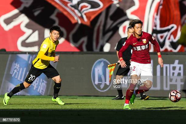 Ding Haifeng of Hebei China Fortune and Yu Hanchao of Guangzhou Evergrande compete for the ball during the Chinese Super League match between Hebei...