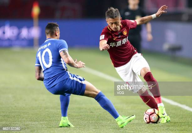 Ding Haifeng of Hebei China Fortune FC and Tjaronn Chery of Guizhou Hengfeng Zhicheng compete for the ball during the 3rd round match of CSL Chinese...
