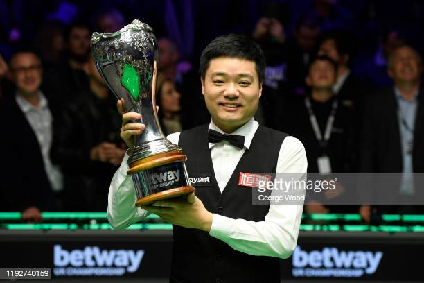 Ding Junhui celebrates with his trophy after winning the final match against Stephen Maguire in the Final of the Betway UK Championship at The...