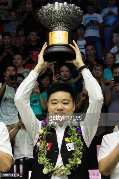 Ding Junhui of China celebrates with his trophy after winning the final match against Kyren Wilson of England on day seven of the World Open 2017 on...