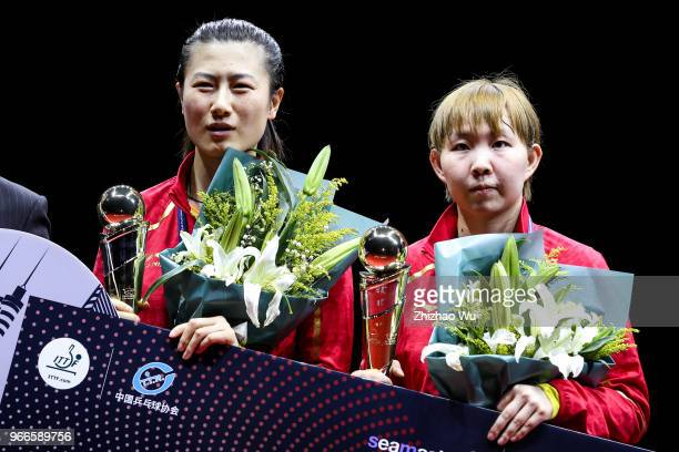 Ding Ning and Zhu Yuling of China attend the award ceremony after their women's doubles final match against Jeon Jihee and Yang Haeun of South Korea...