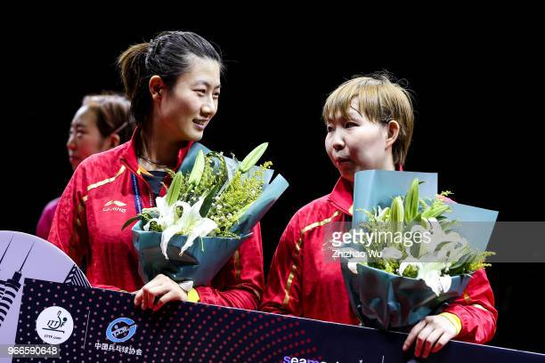 Ding Ning and Zhu Yuling of China attend the award ceremony at the women's doubles final compete with Jeon Jihee and Yang Haeun of South Korea during...