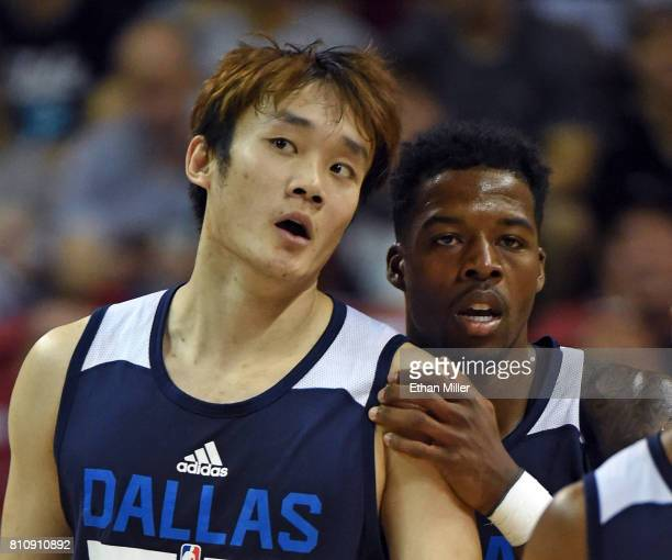 Ding Yanyuhang and Carrik Felix of the Dallas Mavericks walk off the court during a timeout in their 2017 Summer League game against the Chicago...