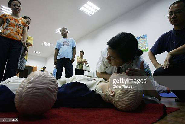 Ding Yimei an emergency room doctor of the Wuhan Medical Emergency Center displays first aid skills to residents during a first aid training session...