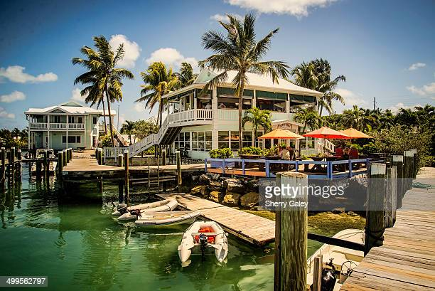 CONTENT] Dinghies line up at a dock beside a tropical restaurant in Marsh Harbour Abacos Bahamas