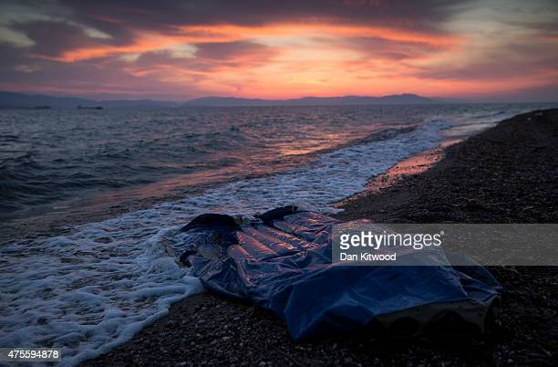 A dinghy is left on the shore after a boat full of migrants arrived in a dinghy shortly before sunrise on June 02 2015 in Kos Greece Migrants are...