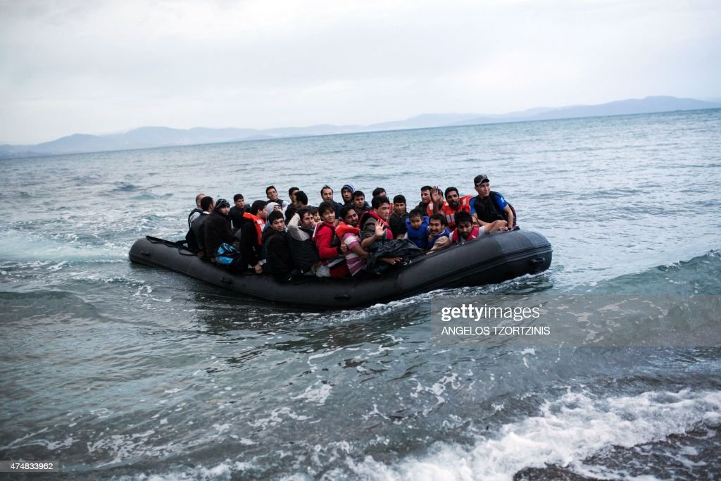 A dinghy overcrowded with Afghan immigrants arrived on a beach on the Greek island of Kos, after crossing a part of the Aegean Sea between Turkey and Greece, on May 27, 2015. AFP PHOTO / Angelos Tzortzinis