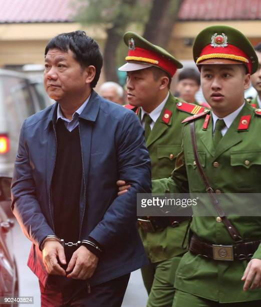 Dinh La Thang former politburo member and former Vietnam's National Oil Company PVN is escorted by policemen to the courtroom at Hanoi People's...