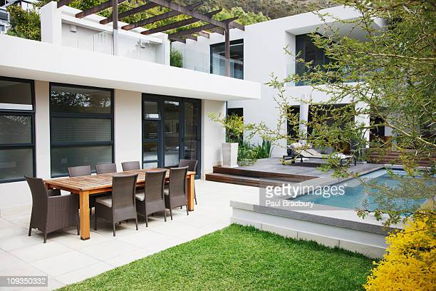 Dining area next to modern house and swimming pool