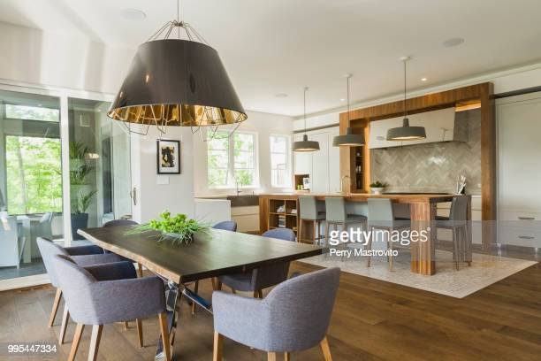 dining room and kitchen area inside a luxurious contemporary home - dining room stock pictures, royalty-free photos & images