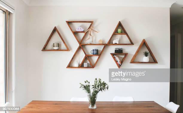 Dining room area with triangle shelves as wall decor