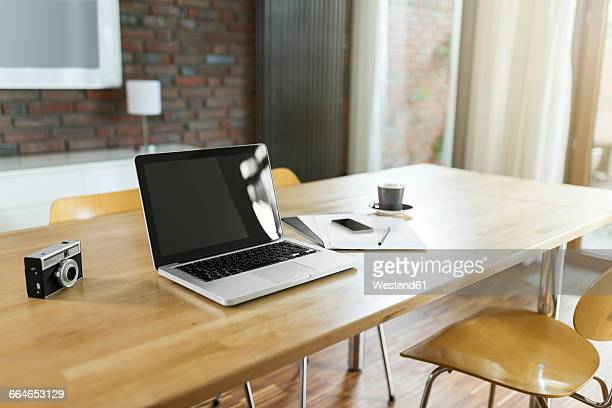 Dining room table with laptop and camera