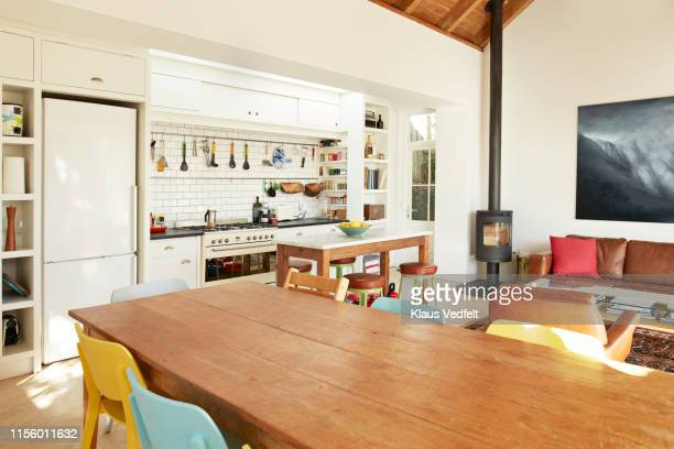 dining table against kitchen counter at home - living room stock-fotos und bilder