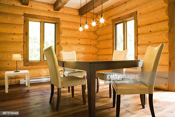 dining table and chairs with modern lighting in eastern white pine log cabin - eastern white pine stock pictures, royalty-free photos & images