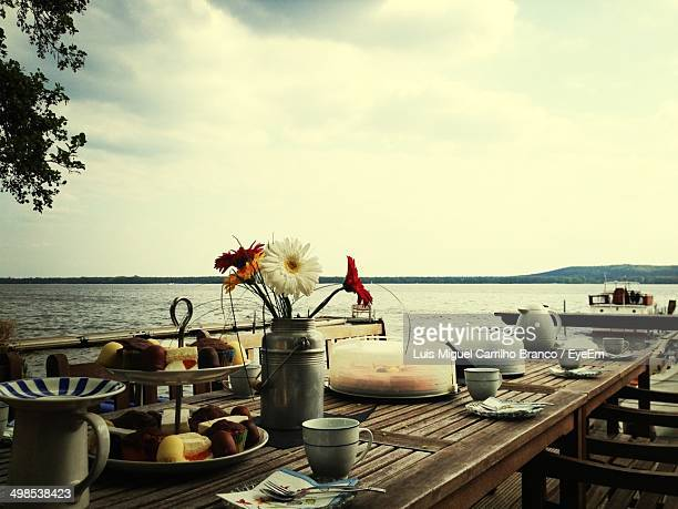 Dining table arranged at restaurant by sea