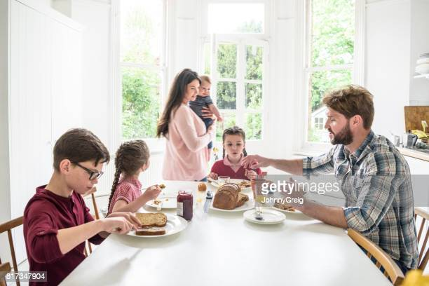 Dining table in modern home with family eating breakfast, mother carrying son