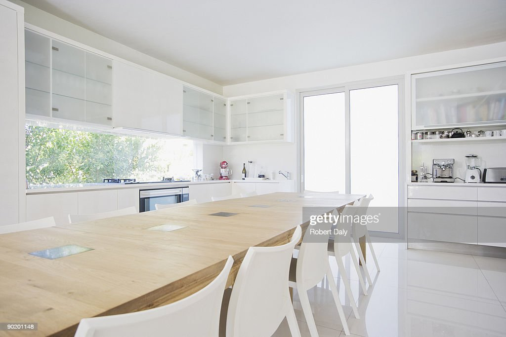 Dining table in modern, white kitchen : Stock Photo