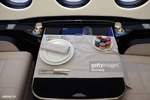 A dining table laid for one person sits between seating in the cabin of a Falcon 7X business jet manufactured by Dassault Aviation SA on the opening...
