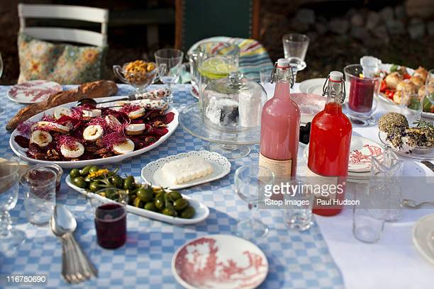 Dining table outside with crockery  and food such as olives and goat's cheese