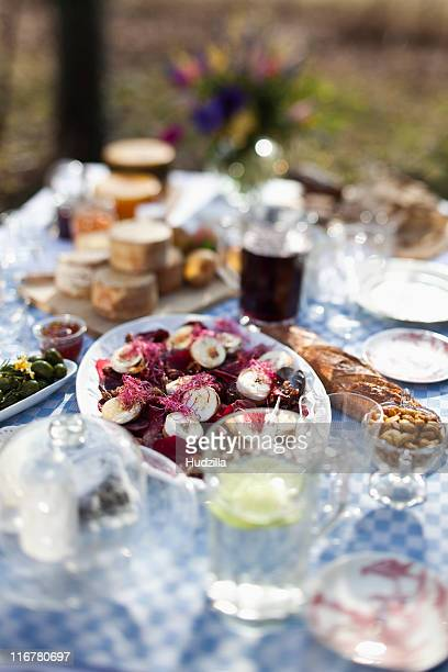 Dining table outside with focus on a dish of goat's cheese and pickled pears
