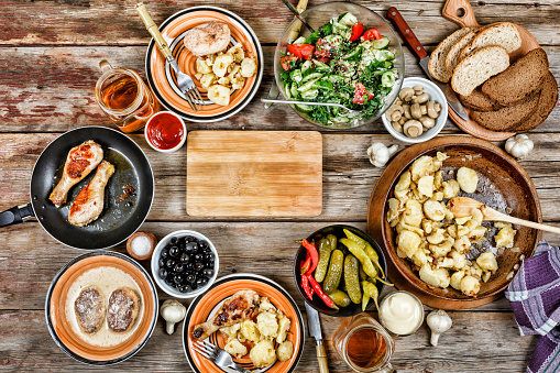 Dining table with a variety of dishes, grilled chicken legs, fried potatoes with vegetables in a frying pan, salad and snacks on a wooden table, top view 883662660