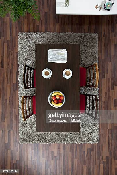 A dining table with coffee cups and newspaper, overhead view