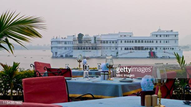 dining tables with lake palace in background - udaipur stock pictures, royalty-free photos & images