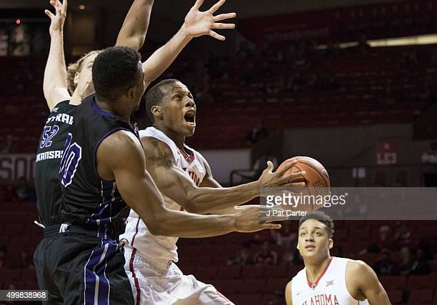 Dinjiyl Walker of the Oklahoma Sooners goes up for a shot against Mathieu Kamba of the Central Arkansas Bears during the second half of a NCAA...