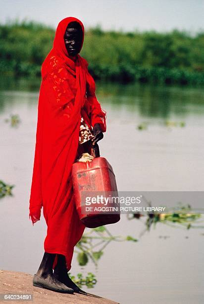 Dinka woman with a jerry can at a body of water South Sudan