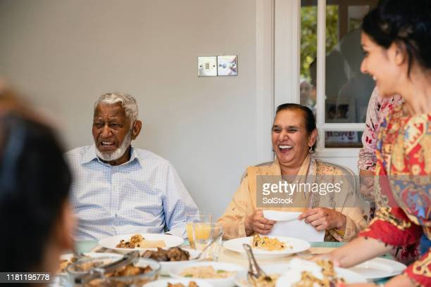 dinner and laughing - indian culture stock pictures, royalty-free photos & images